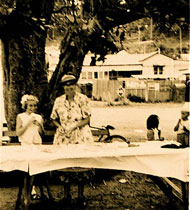 Mrs Radford, also know as Granny Radford, setting up tables under the coral tree in the square at Wagstaffe, in preparation for a stall or a party.
